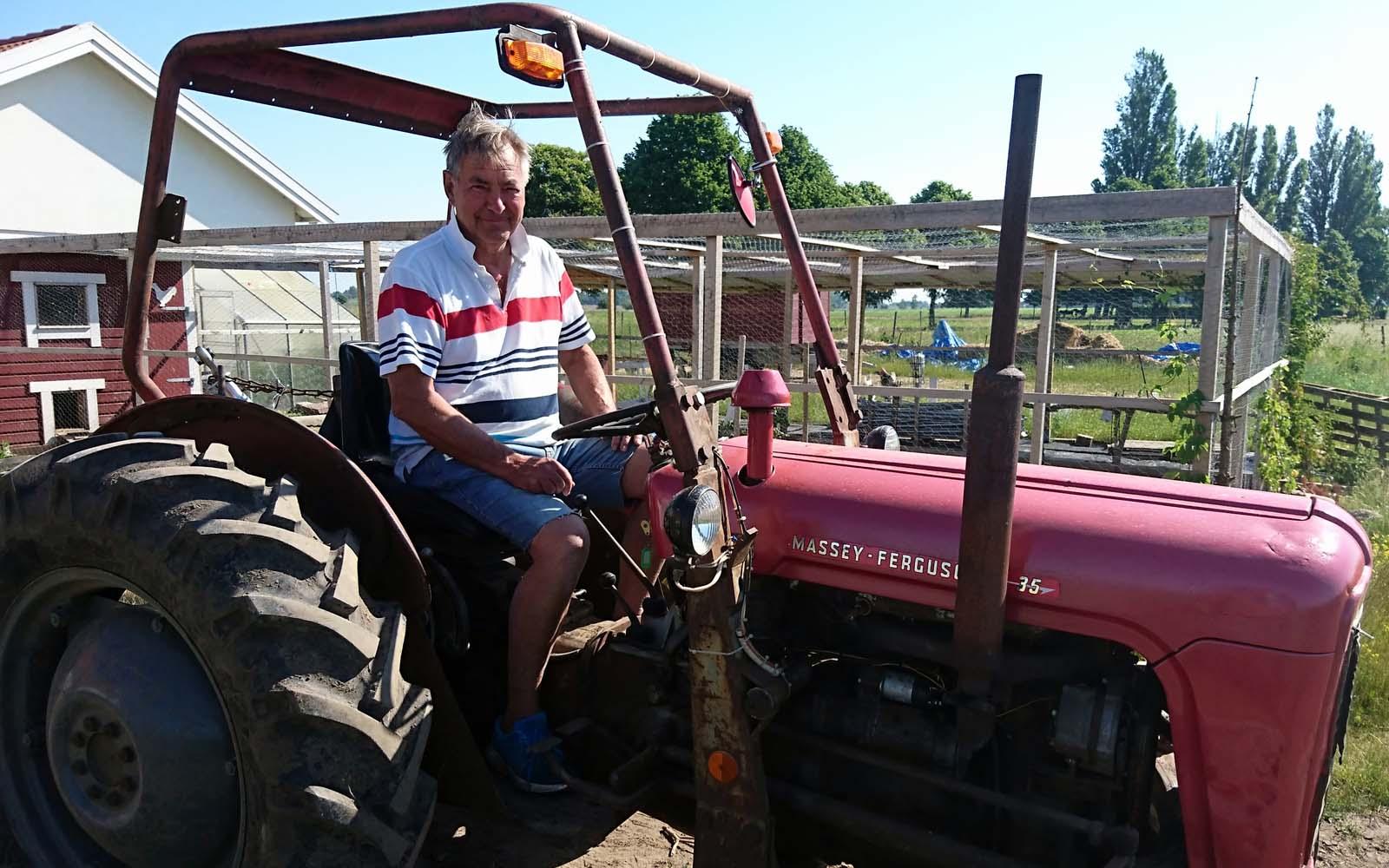 Staffan Broddesson tar en tur med traktorn medan sonen arbetar med annat